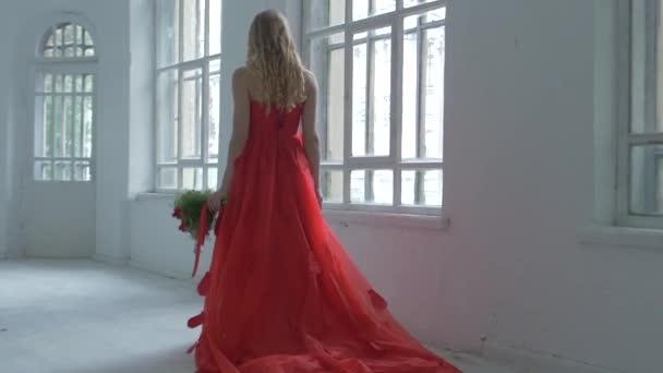 Hezká dívka v nádherné červené šaty, prochází kolem historických oken s květinami a její vlasy, zpomalené vlny