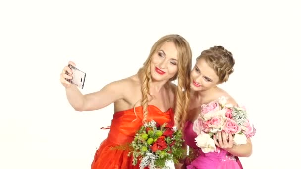 Two beautiful girls in gorgeous dresses taking selfie, on white, slow motion