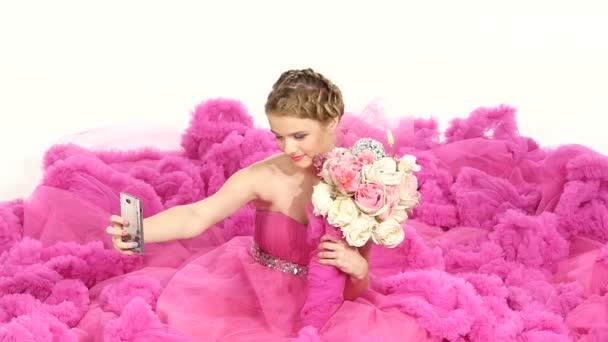 Hezká mladá žena v nádherné růžové šaty, sedící, vůně květin, což selfie, na bílé, Zpomalený pohyb