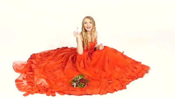 Csinos, fiatal lány, gyönyörű piros ruha ül, fújó, mosolyogva, elszigetelt fehér, lassú mozgás