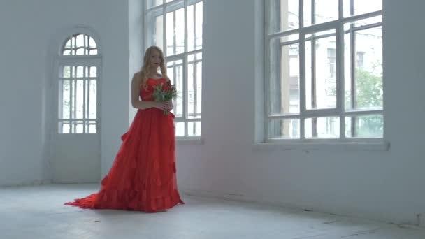 Hezká dívka v nádherných červených šatech chodit kolem historických oken s květinami, zpomalené