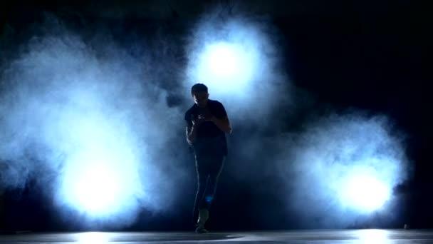 One hip hop break-dancer stylish man dancing, smoke, silhouette