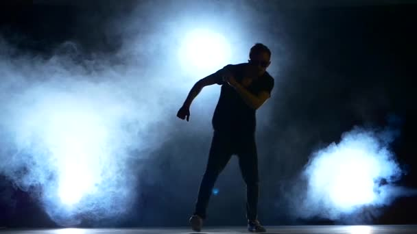 Young hiphop dancer making a move, jump, smoke, silhouette, slow motion