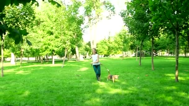 Happy young woman jogging with her beagle dog. Slow motion