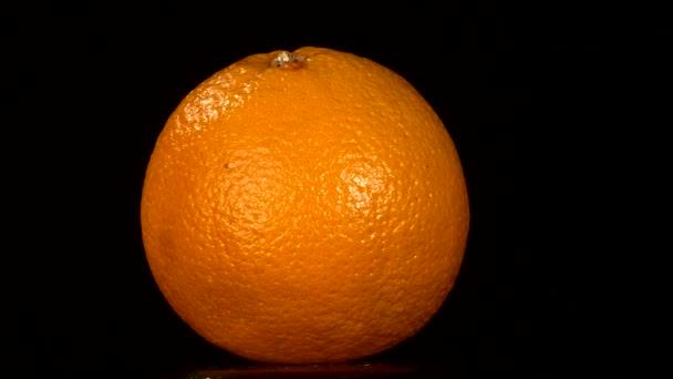 Zralé oranžové izolované na černou, rotace