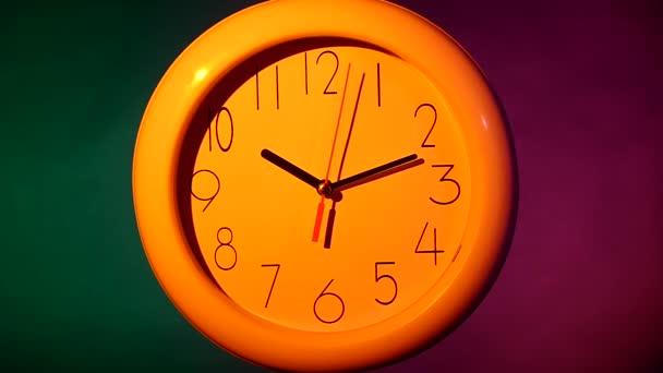 bílé hodiny na barevné pozadí. Zpomalený pohyb