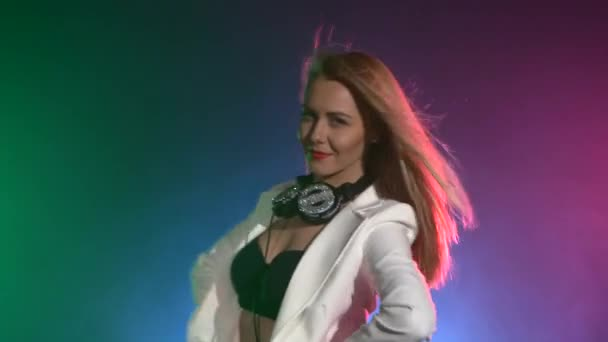 Beautiful, charming, smiling dj girl in white jacket, headphones on her ears, playing, listening music and dancing, smoke, the camera shoots up to waist, and hands on it