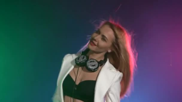 Beautiful, charming, smiling dj girl in white jacket, headphones on her ears, playing, listening music and dancing, smoke, the camera shoots up to waist