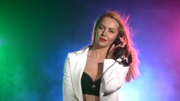 Beautiful, charming, smiling dj girl in white jacket, headphones on her ear, playing, listening music and dancing, smoke, the camera shoots up to waist, green, blue, pink