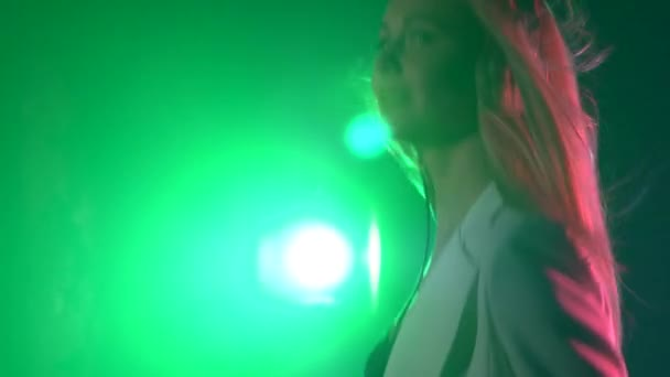 Beautiful, charming, smiling dj girl in white jacket, headphones on her ear, playing, listening music and dancing, smoke, green backlight, hand in her pocket, cam moves upward