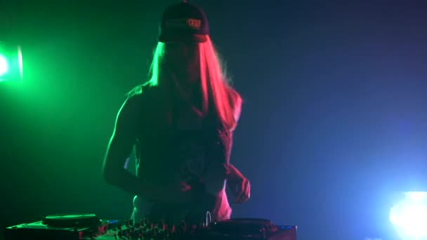 Beautiful, sexy dj girl in cap, headphones playing music and dancing, hand in the pocket, smoke, silhouette