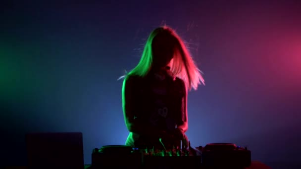 Attractive dj girl in sexy clothes, dancing, flipping hair, hands up, enjoy it,  using headphones, smoke, backlight, silhouette