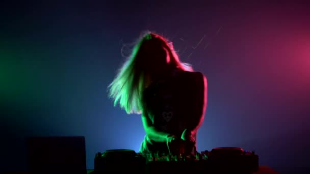 Attractive, smiling dj girl in sexy clothes, flipping hair, hands up, enjoy it,  using headphones, smoke, backlight, silhouette