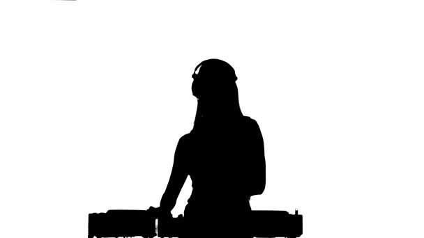 Dj girl in sexy clothes, flipping hair, hand up, dancing using headphones, silhouette, on white
