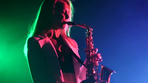 Young sexy, blonde woman dj in white jacket and black top playing music using saxophone, flipping hair, dancing, cam moves upwards, on green and blue