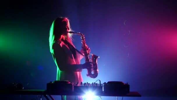 Young sexy, blonde woman dj in white jacket and black top playing music using saxophone, flipping hair, dancing, on green, pink and blue, backlight