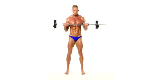 shirtless kulturista zvedání těžkých činka hmotnosti v tělocvičně