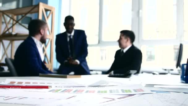 Tři obchodní lidé diskutují o myšlenkách, debatovali. Zaměřit se na dokumentaci.