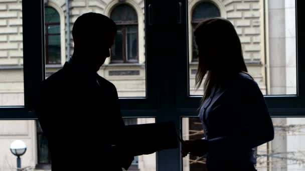Girl shows document to a colleague on  plate standing at the window. Silhouette