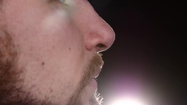 Young man to trim his mustache and beard. Master works very carefully. Slow motion. Close up