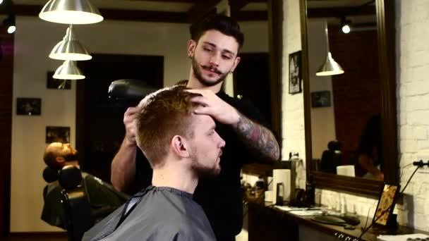 Stylový interiér: Barber vysouší vlasy klienta, při pohledu na sebe do zrcadla