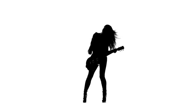 Silhouette of a young girl playing dancing on electric guitar on a white background.
