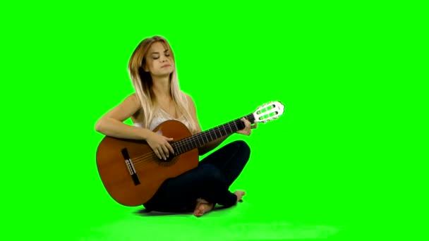 Young beautiful caucasian woman in casual playing guitar. Green screen