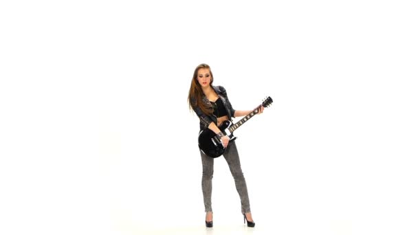 Beautiful young girl playing on electric guitar on a white background. Slow motion.