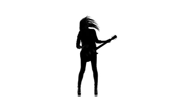 Silhouette of a young girl playing on electric guitar on a white background. Slow motion.