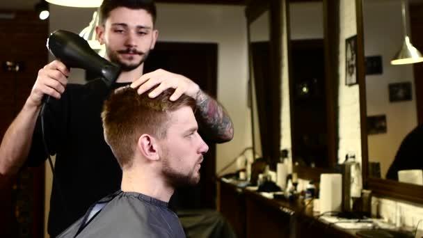 Stylový interiér: holič vyschne ve vlasech a dívá se na sebe. Zpomaleně