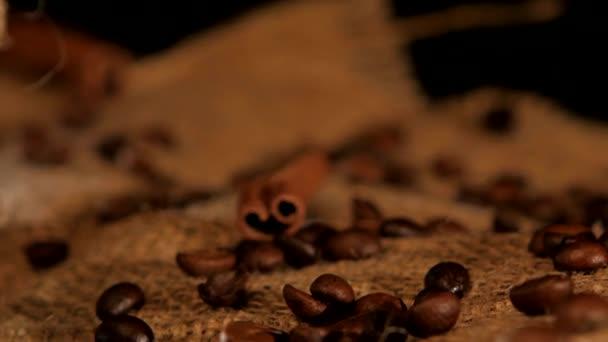 Kávébab fahéjjal a kávésüveg közelében fekete alapon, elforgatás