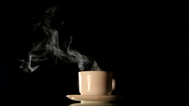 Steaming white coffee cup on black background