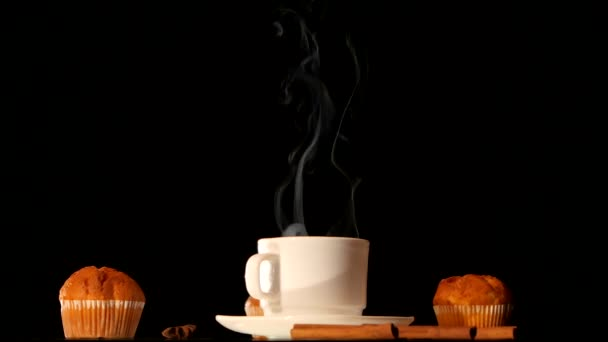 White steaming coffee cup with cakes, anise, cinnamon on black background