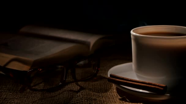 Hot coffee and book with glasses, cinnamon on sacking, black background