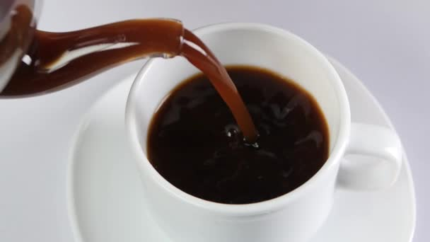 Pouring coffee into a cup on white background, slow motion