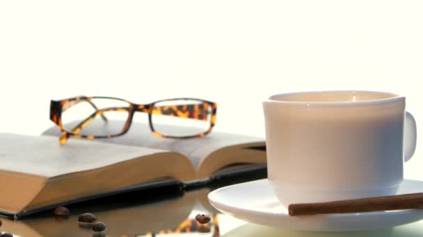 Delicious coffee and book with glasses, cinnamon, beans on white background