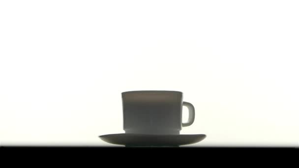 Pouring splashing coffee in cup on white background, slow motion