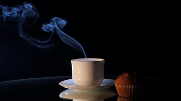 Cup of hot coffee with muffin on black background