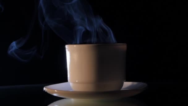 Cup of smoking coffee isolated on black background, close up