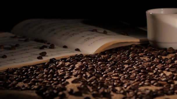 Aromatic coffee beans with music on sacking, black background, slow motion