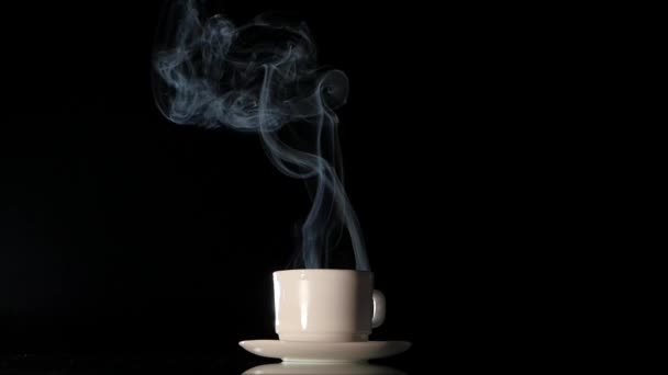Cup with hot smoking coffee on black background