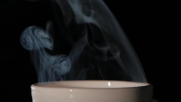 Top of cup with hot coffee on black background