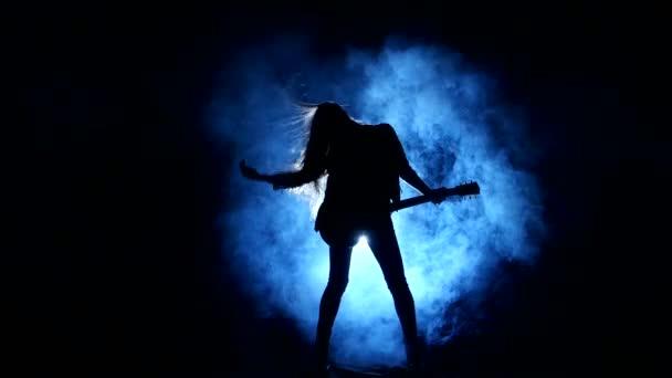 Sziluettje egy fiatal lány játszik az elektromos gitár.
