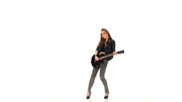 Gyönyörű fiatal lány játszik az elektromos gitár fehér alapon. Lassított mozgás.