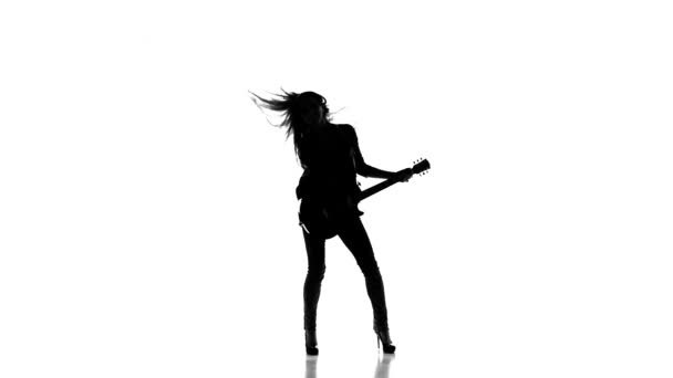 Silhouette of a young girl dancing with electric guitar on a white background. Slow motion.