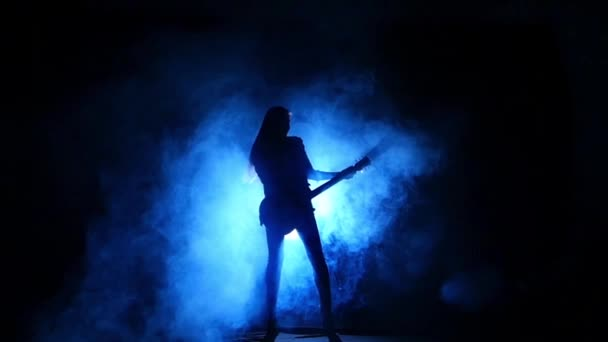 Silhouette of a young girl playing on electric guitar. Slow motion.