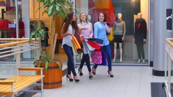 Three beautiful girls with shopping bags goes on shopping center. Slow motion.