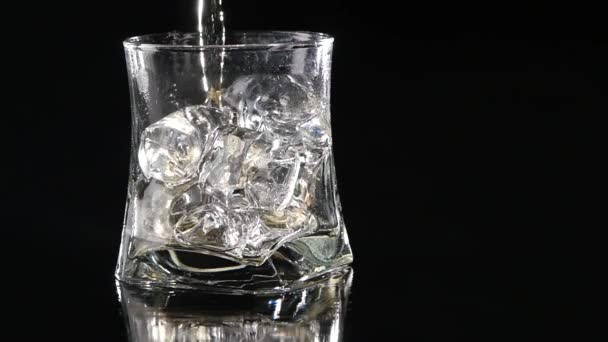 Whiskey being poured into a glass against black background. Close up. Slow motion.