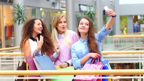 Group of happy best friends with shopping bags taking a selfie in the city  - Girlfriends walking and having fun in the summer around the old town - University students during a break in a sunny day