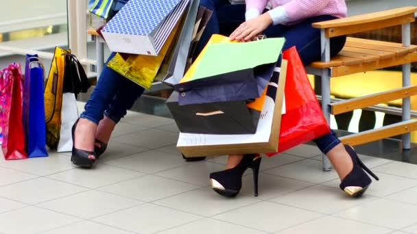 Two beautiful girls with shopping bags watch purchase on shopping center